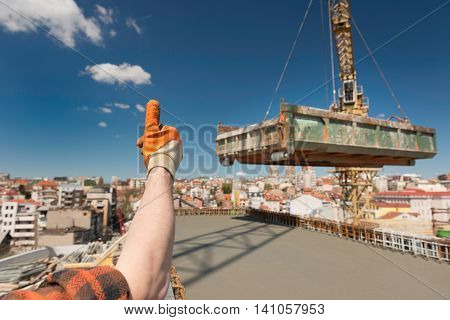 Construction worker signaling to crane operator, horizontal
