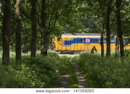 Dutch train passing by on a not secured railway crossing near Ellecom in the Netherlands