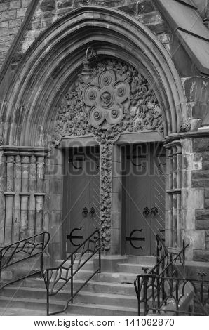 A view of the wooden doors and elaborate masonry of a church entrance in Dunfermline