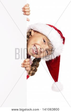Happy little Santa Claus. Smiling Christmas little girl in red Santa hat peeking from blank board, isolated on white background. Space for text.