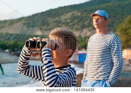boy in garrison cap and striped vest standing near the sea with binoculars next to his father in the background of the mountains