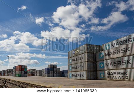 DONCASTER, YORKSHIRE, UK - JULY 30, 2016. Cargo an shipping containers stacked on top of each other in a railway depot before being loaded onto goods trains for onward travel to Uk ports and docks for export.
