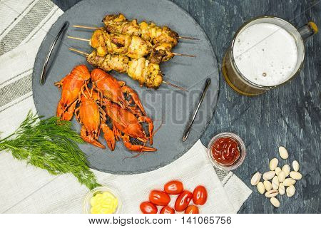 Top view of Tasty boiled crayfishes barbecueand and beer on wooden table with vegetables and sauce. Flat lay overhead view. Concept snacks