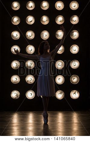 Dance. Ballet dancer is dancing in the dark hall with lamps. Yuong women ballerina exercising. Young girl standing on pointe in dance position