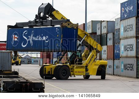 DONCASTER, YORKSHIRE, UK - JULY 30, 2016. A heavy lifting machine loading cargo and shipping containers onto goods trains at Doncaster Railport for onward travel to UK ports and docks for export.