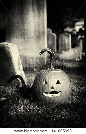 A jack-o'-lantern pumpkin in a graveyard surrounded by old tombstones. Black and white filter with film grain and vignette applied.