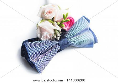 blue plaid bow tie lies next to the groom's boutonniere isolated on a white background. Wedding concept. bridegroom's pastel accessories such as bow-tie and flowers on the marriage day.