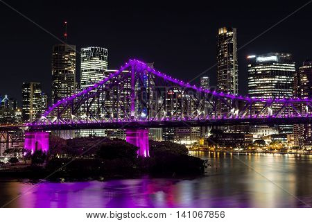 BRISBANE, AUSTRALIA: Brisbane Story Bridge southern side (magenta) and cityscape closeup by night viewed from the New Farm Riverwalk