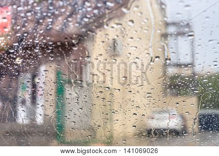 driving car in rain - rain trickles on windscreen and blurred house on background