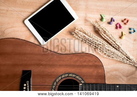 Top view of acoustic guitar with tablet touch computer gadget on wooden table background.