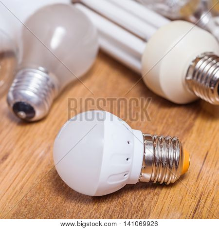 One New Led Lamp And Pile Of Used Bulbs On Board