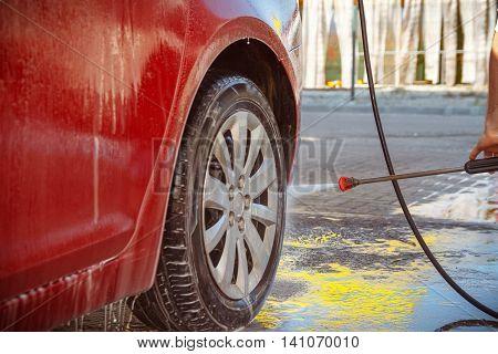 Contactless car wash self-service. Young man washing his car