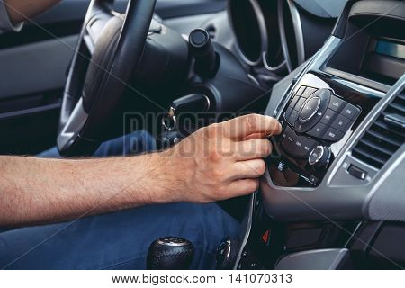 Car dashboard. Radio closeup. Man sets radio