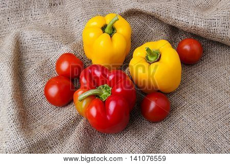 Tomatoes and bell-peppers on a rustic jute cloth