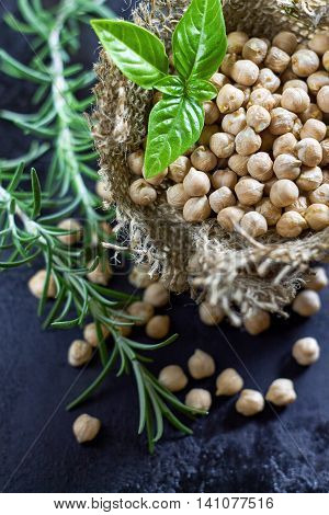 Garbanzo beans (chickpeas) with basil in small burlap bag on black rustic background. Top view