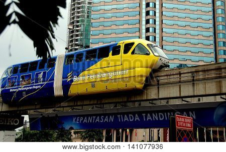 Kuala Lumpur Malaysia - December 25 2007: A KL Monorail train zips along its elevated trackbed passing the luxury Renaissance Hotel *