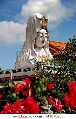 Penang Malaysia - January 8 2008: An immense Guan Yin Buddha statue and red Bougainvillea flowers at 1891 Kek Lok Si Temple