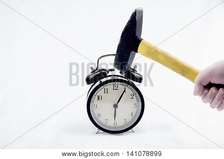 Close up view of hammer is crashing alarm-clock