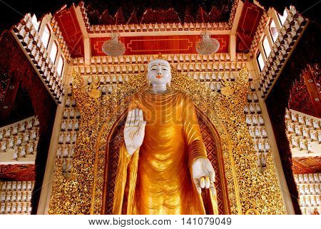 Georgetown Malaysia - January 82008: A benevolent gold-robed giant alabaster Buddha in the great hall of the Dhammikarama Burmese Buddhist Temple