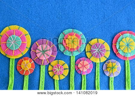 A row of colorful flowers on blue felt. Home bright flowers made of felt circles. Background for greeting card for birthday, Valentine's day, Easter, mother's day. Top view with copy space