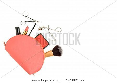 Top view of pink cosmetic bag consist of makeup brush lipstick brush on scissors mascara eyelash curler - isolated make up items on white background