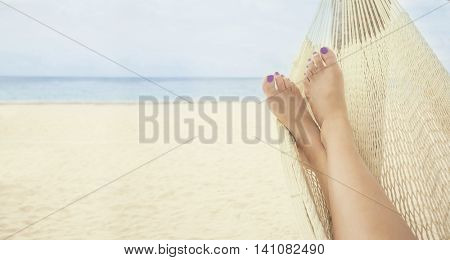 Beautiful female feet relaxing in a hammock on the beach horizontal