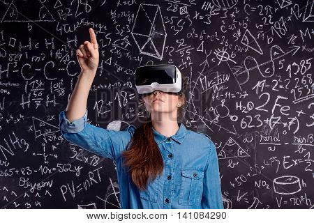 Beautiful woman in blue denim shirt wearing virtual reality goggles, pointing up with finger. Student against big blackboard with mathematical symbols and formulas. Studio shot on black background.