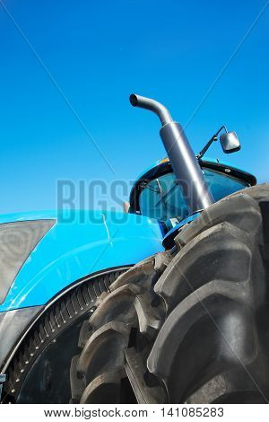 Tire on blue tractor close up in the foreground