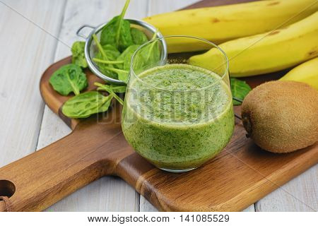 On a wooden chopping board with a light background the Ingredients spinach, buttermilk, kiwi and banana for a tasty smoothie.