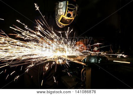 a guy in welding helmet and gear grinding metal done with a long shutter exposure to show the sparks in the dark