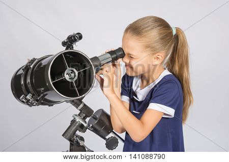 Seven-year Girl Squinting With Interest Looks In A Reflector Telescope