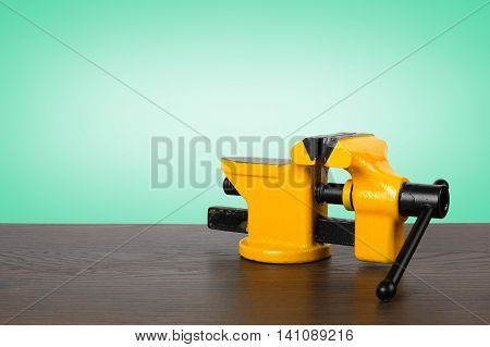 The metalwork tool - Yellow with black a vise on a wooden table and a green background.