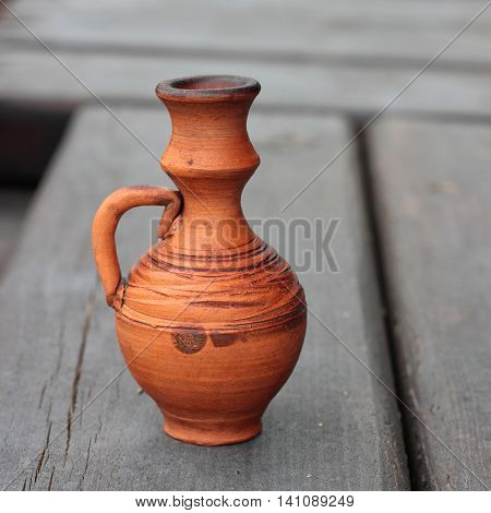 Storage for liquids - Old Vintage jug ewer on darkly brown wooden background.