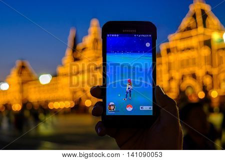 Moscow - July 31: Male hand holding a Samsung Galaxy smartphone with a running Pokemon Go application at night