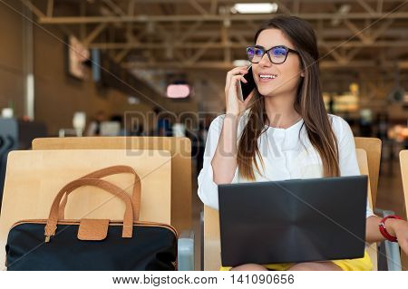 Airport Young female passenger on smart phone and laptop sitting in terminal hall while waiting for her flight. Air travel concept with young casual woman sitting with hand luggage suitcase.
