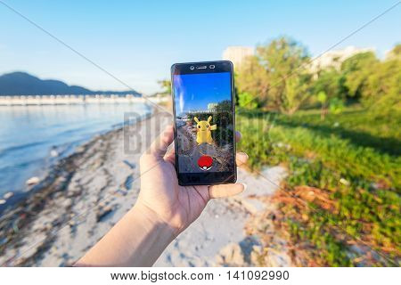 California, United States - July 2016 : Hand holding a cellphone to play Pokemon Go with blur beach background