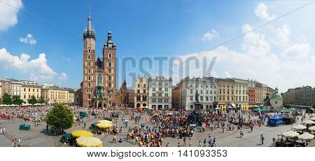 KRAKOW POLAND - JULY 27 2016: Main Market Square (Rynek) and St Mary Church in Cracow during the World Youth Day 2016. Young people gathered around the monument of Adam Mickiewicz. Wide panorama