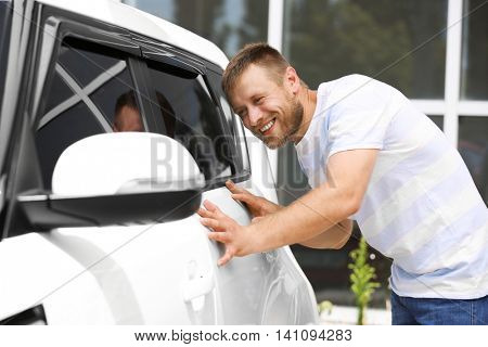 Man examining new car outdoors