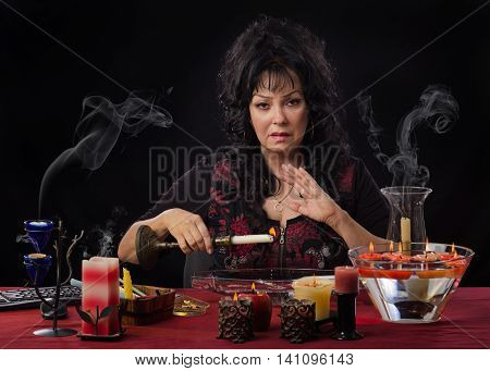 Stunning middle-aged female psychic holds burning candle over long glass bowl filled water. The fortuneteller allows the candle wax to drip into the water. She sits at the desk surrounded by burning candles and looks at the camera