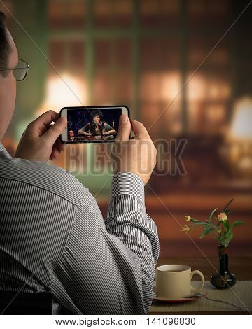 Middle aged man sits in cafe and looks at a touchscreen of mobile phone. There is a clairvoyant predicting the future during online session. Vertical indoors back shot on blurry background