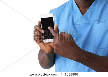 Professional African doctor with cellphone on light background