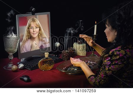 Fortuneteller teaches online young blonde girl how to attract love with rose quartz. This psychic uses semi-precocious gemstones for prediction. Naive long-haired girl looks intently to middle aged clairvoyant