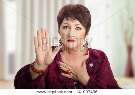 Middle aged woman in maroon blouse shows right hand and looks at the camera. It seems woman in dark brown wig either pleads or swears. Horizontal indoors upper body shot