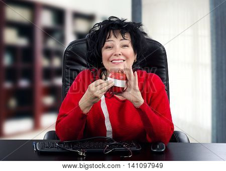 Smiling doctor in red jumper explains how to measure body waist. Black-haired mature physician uses red apple and meter for clarification