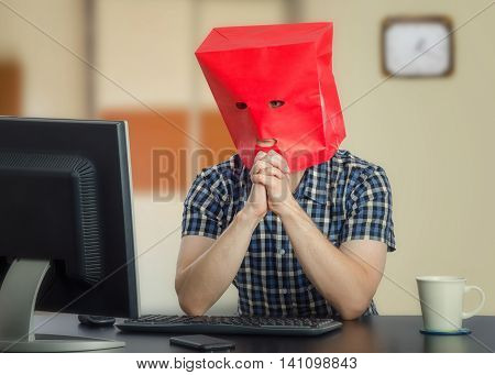 Introverted young man in red paper bag is frightened at first time online dating. His hands are clenched in front of the face