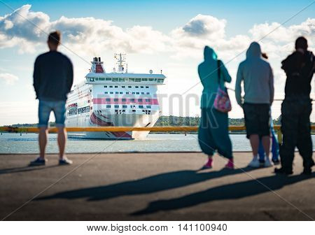 Big ferry ship arriving in port of Turku Finland Scandinavia Europe. Liner with blue cloudy sky in background and people waiting in foreground.