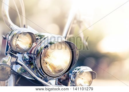 Motorcycle detail with headlamps in foreground and blurred nature background. Travel by motorbike.