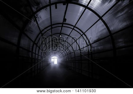 Dark sinister tunnel with shadows on the walls and the light at the end of it