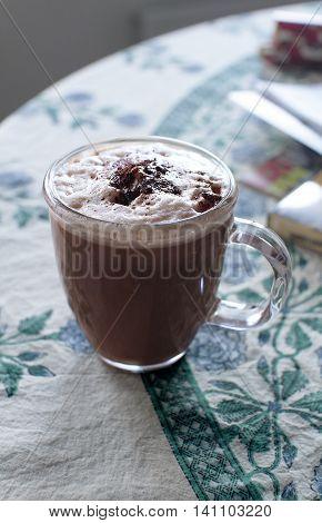 A glass mug of cappuchino on a table