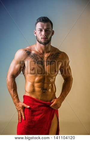 Handsome shirtless muscular man, standing, in studio shot with towel around his waist
